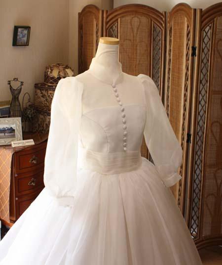 ハイネックとパフスリーブを施した上半身デザイン。クルミボタンを施したクラシックスタイルのドレス